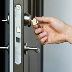 door lock service - locksmith working in red uniform